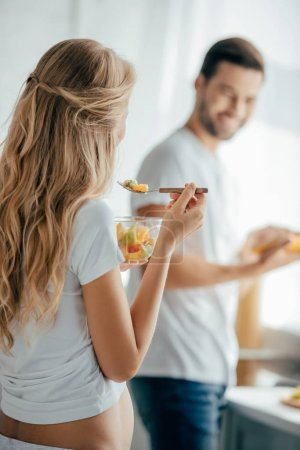 Photo for Selective focus of pregnant woman eating fruits salad while smiling husband standing at counter in kitchen - Royalty Free Image