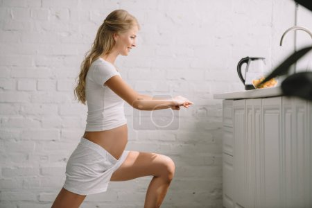 side view of smiling pregnant woman doing fitness exercises at home
