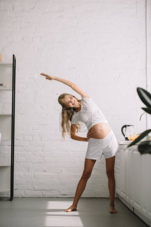 cheerful pregnant woman doing fitness exercises at home