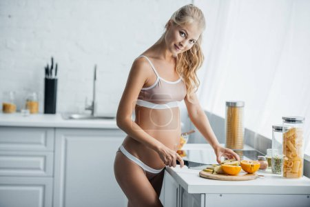 pregnant woman preparing fruits salad at counter in kitchen at home
