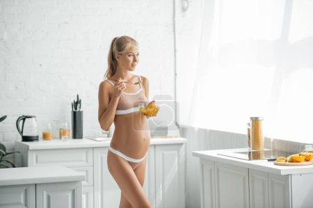 pregnant woman in underwear with bowl of fresh fruits salad in kitchen at home