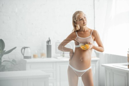 pregnant woman in underwear akimbo with bowl of fresh fruits salad in kitchen at home