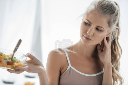 portrait of woman feeling discomfort while looking at bowl with fruits salad at home