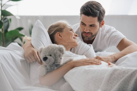 Photo for Pregnant woman in white nightie with teddy bear on sofa and husband near by at home - Royalty Free Image