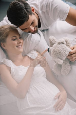 portrait of man with teddy bear and smiling pregnant wife in white nightie on sofa at home