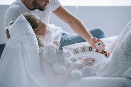 partial view of man putting wooden blocks with baby lettering on belly of pregnant wife with teddy bear at home