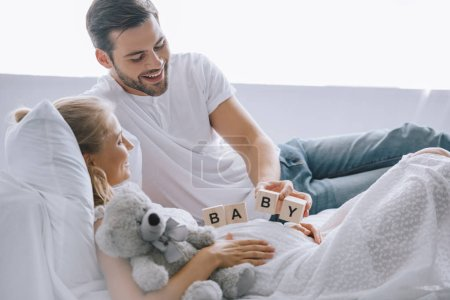 smiling man putting wooden blocks with baby lettering on belly of pregnant wife with teddy bear at home