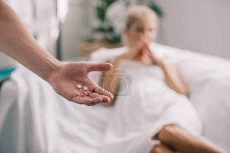 cropped shot of man with pills in hand and pregnant woman feeling discomfort at home