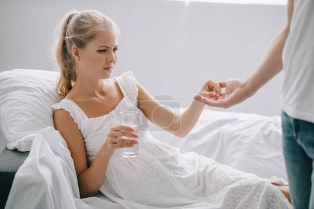 partial view of man giving medicines to pregnant woman in white nightie on sofa at home