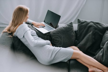 pregnant woman using laptop with blank screen on sofa at home