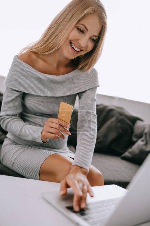 sonriente mujer embarazada con tarjeta de crédito y laptop comprar mercancía en línea en casa