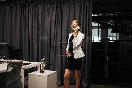 Photo for Pregnant businesswoman in formal wear talking on smartphone in office - Royalty Free Image