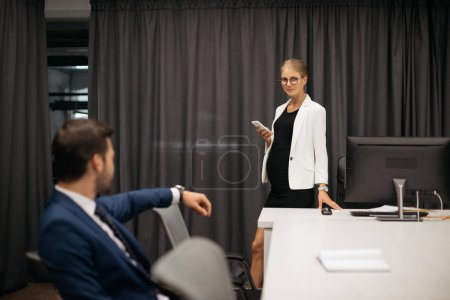 selective focus of businesswoman with smartphone and colleague at workplace in office