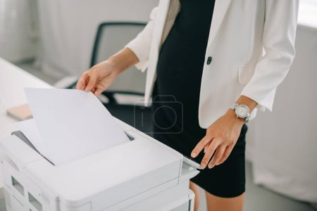 Photo for Partial view of pregnant businesswoman using printer in office - Royalty Free Image
