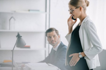 smiling pregnant businesswoman talking on smartphone while standing near colleague at workplace in office