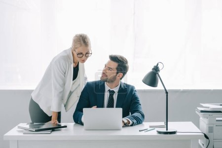 portrait of business colleagues using laptop at workplace in office