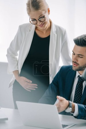 portrait of pregnant businesswoman and colleague at workplace with laptop discussing project in office