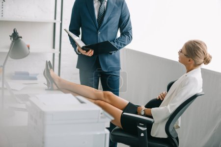 businessman with documents and pregnant colleague discussing work at workplace in office