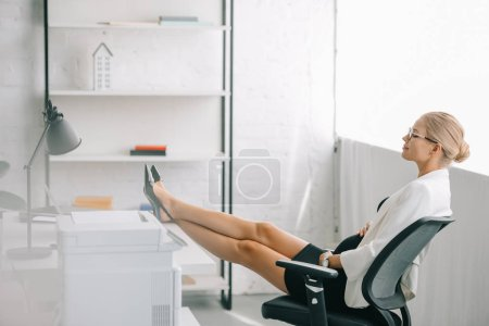 side view of pregnant businesswoman resting with legs on table at workplace in office