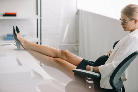 Photo for Side view of pregnant businesswoman resting with legs on table at workplace in office - Royalty Free Image