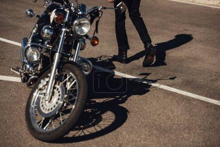cropped view of male biker going near classical chopper motorbike