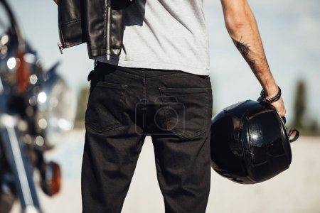 midsection view of male biker holding motorbike helmet