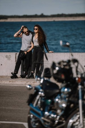 selective focus of young couple with motorcycle on foreground