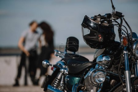 selective focus of classical motorcycle with bikers on background