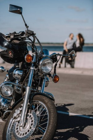 selective focus of classical chopper motorbike with couple on background