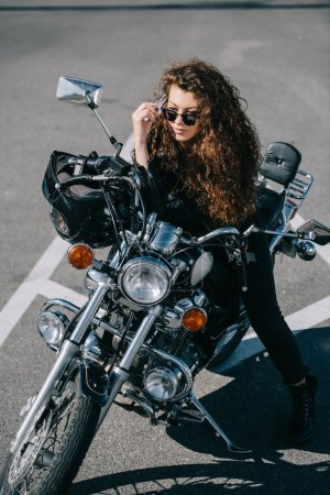 Photo pour Biker femme belle, assis sur la moto sur un parking - image libre de droit