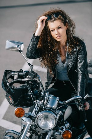 beautiful woman sitting on motorcycle with helmet