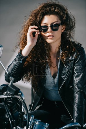 beautiful curly girl in sunglasses sitting on motorbike