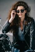 beautiful curly girl in sunglasses sitting on motorbike