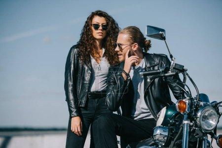 Photo pour Couple de motards en vestes en cuir assis sur moto vintage classique - image libre de droit