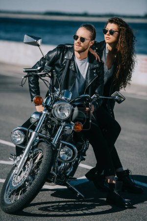 Photo pour Couple de motards en cuir noir vestes assis sur moto classique - image libre de droit