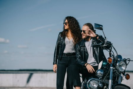 bikers in black leather jackets sitting on chopper motorcycle