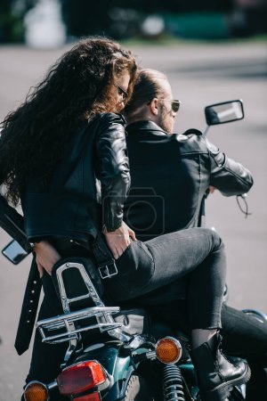 back view of couple of bikers in black leather jackets sitting on motorcycle