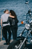 back view of young couple hugging near the sea with motorcycle on foreground