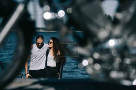 couple hugging and going to motorbike on foreground, selective focus