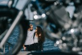 couple of bikers hugging and going to motorbike on foreground, selective focus