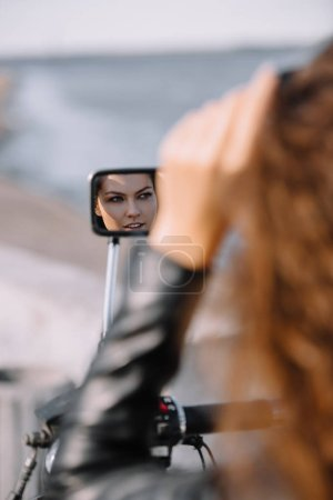 reflection of beautiful woman in mirror of motorcycle