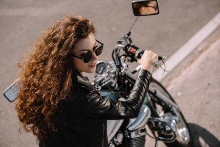 beautiful girl sitting on classical motorbike on parking
