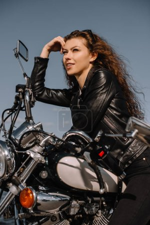 attractive female biker sitting on vintage classical motorbike