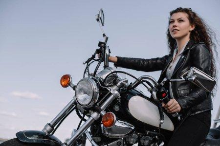 Photo pour Belle motard femme assise sur moto vintage - image libre de droit