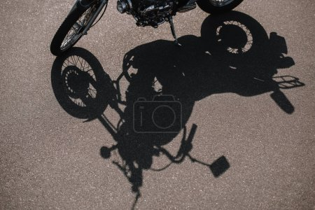 cropped view of motorbike with shadow on asphalt road
