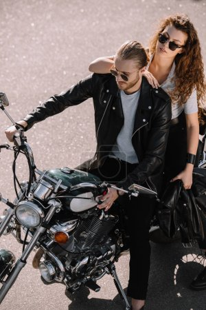two bikers sitting on classical cruiser motorcycle on asphalt road