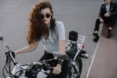 woman sitting on classical cruiser motorcycle while her boyfriend sitting on asphalt road