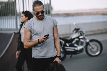 man in sunglasses using smartphone while girlfriend standing with classical motorbike on background