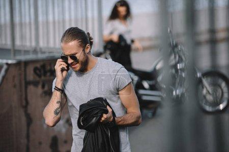 homme parle sur smartphone tout en jeune fille debout avec une moto classique