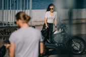 selective focus of biker going to girlfriend with vintage motorbike